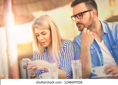 Jealous man looking  in girlfriend phone while she texting  a message, relationship problem