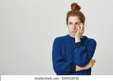 Jealous sister is offended that she did not got present. Gloomy annoyed redhead female student in winter sweater, turning head aside and leaning on palm, sulking and puckering being angry at someone