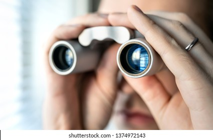 Jealous and suspicious man suspecting  wife cheating and having an affair. Obsession, doubt, paranoia and jealousy in relationship concept. Over protective and controlling husband with binoculars.
