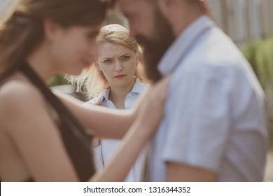 A jealous wife. Unhappy girl feeling jealous. Romantic couple of man and woman dating. Bearded man cheating his girlfriend with another woman. Jealous woman look at couple in love on street.