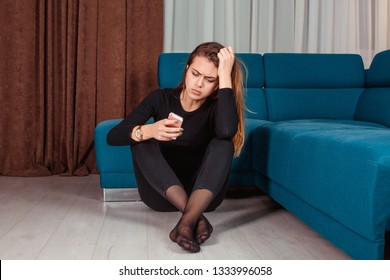 Jealous woman sitting near sofa holding phone feeling sad waiting for call, frustrated millennial girl upset, worried receiving bad news in mobile message on smartphone at home. Cyber-bullying concept