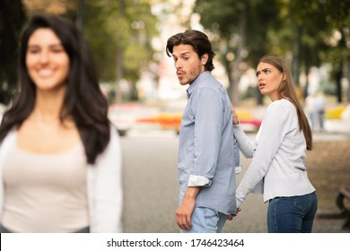 Jealousy. Jealous Girlfriend Calling Boyfriend Distracted By Other Attractive Woman Walking During Date In Park. Selective Focus