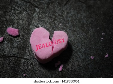 Jealousy text on a pink candy heart