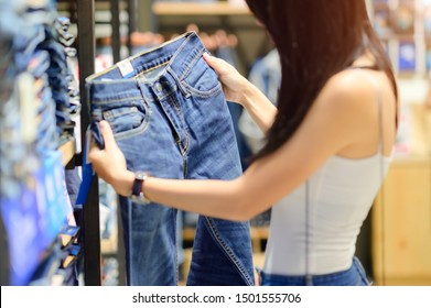 Jean pants in hand od woman shopping, select shooting a right size fitting before buy