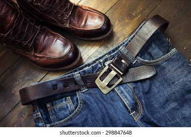Jeans belt and shoes set on wooden board