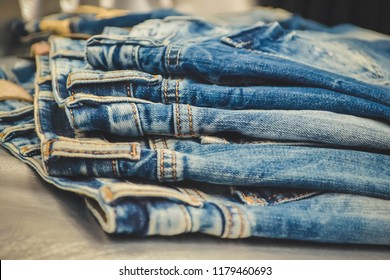 Jeans, clothing, denim. Detail of nice blue jeans vintage style. Denim pants pocket stack or store cloth fashion textile cotton with old torn. Casual grunge trousers apparel.