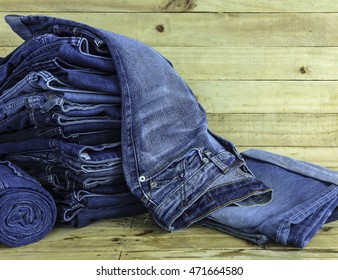 jeans denim pile on a wood background.