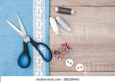 Jeans fabric for sewing, lace and accessories for needlework on old wooden background. Spool of thread, scissors, buttons, sewing supplies. Set for needlework top view