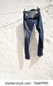 Jeans hung on a white wall.