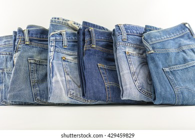 Jeans on a white background./ Jeans folded stacked layers.