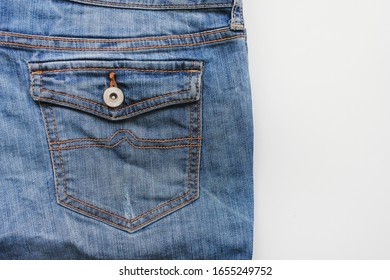 Jeans pocket on classic blue denim pants. Stylish blue jeans backside view with buttoned pocket, unisex casual bottoms detail, close up top view of blue jeans design