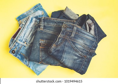 Jeans set of different colors stacked on a yellow background, top view with a copy of the workspace, a concept of a trendy retro style