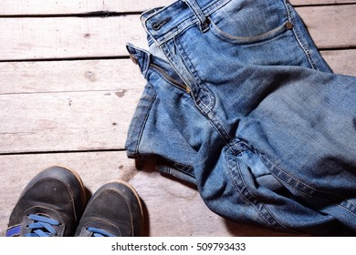 Jeans with shoe over wooden black background.