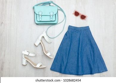 Jeans skirt, glasses, white shoes and handbag. Fashionable concept. Wooden background.