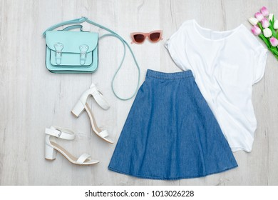 Jeans skirt, white t-shirt, shoes and tulips. Fashionable concept. Wooden background.