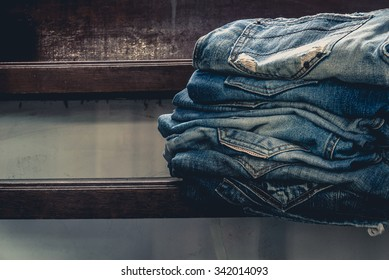 jeans stacked on a urban grange wooden background