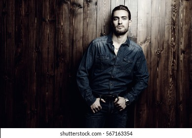 Jeans style. Portrait of a handsome young man in jeans clohes standing against wooden wall. Men's beauty, fashion. Men's barbershop, Hairstyle.