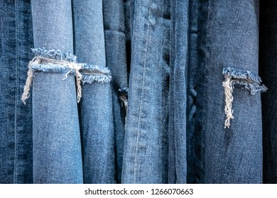 Jeans torn hanging for display in store. Jeans torn at the knee close up