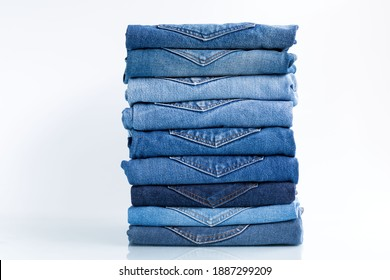 Jeans trousers stack   on a white background concept jeans in supermarket and shop.