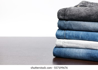 Jeans variations background. Stack of jeans on wooden background with empty space