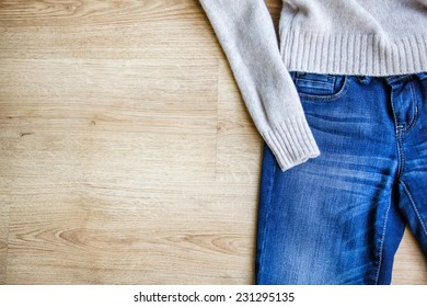 Jeans and woolen pullover on wooden background