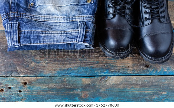 Jeans and work shoes. Haberdashery. Top photo of pants. Elements dressed on boards.