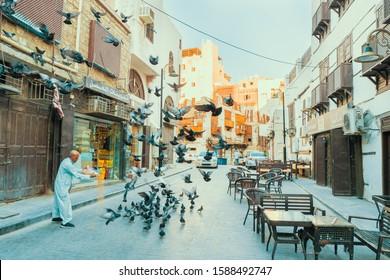 Jeddah, KSA - December 7th 2019: Arabic senior feeding pigeons in a street at the historic district Al Balad in Jeddah, Saudi Arabia