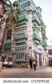 Jeddah / Saudi Arabia - January 16, 2020: Mother and daugther walking in front of historic colorful building in Al-Balad
