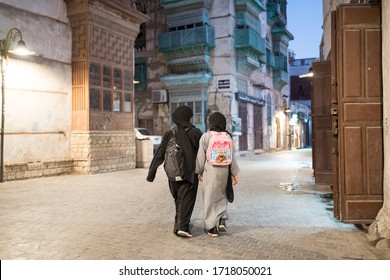 Jeddah / Saudi Arabia - January 16, 2020: Muslim girls with backpacks walking after school in the street of historic Al-Balad