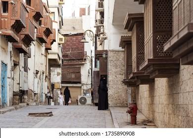 Jeddah / Saudi Arabia - January 16, 2020: Muslim woman wearing black abaya and niqab walks on the streets of the historic center of Al-Balad