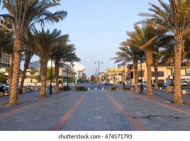 JEDDAH, SAUDI ARABIA - MAY 20, 2017. Romantic sunset light at Jeddah Corniche, nice palm trees and traffic jam in the back