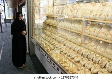 Jeddah, Saudi Arabia - October 27th 2009: Woman wearing an abaya longing for the gold in a shop window