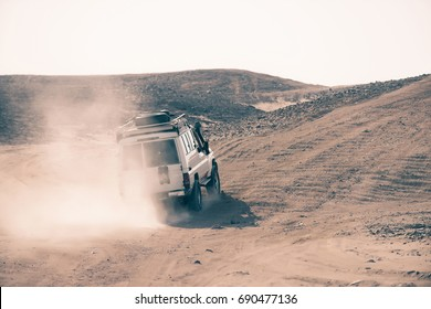 Jeep bashing through dusty sand dunes in desert on white sky background. Safari trip. Offroad adventure. Extreme activity. Travel, travelling. Summer vacation