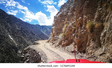 A Jeep Ride on the dangerous and serpentine road in a rock mountain to Fairy Meadows, Nanga Parbat, Karakorum, Northern Area Of Pakistan with background of blue sky and dramatic cloud