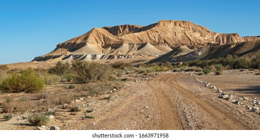 the jeep road running through the nahal zin stream bed in the negev in israel with stunning barren desert mountains and blue sky in the background