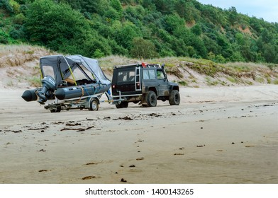 jeep with trailer and boat on the beach, boat on trailer at the car, Baltic sea coast, Kaliningrad region, Russia, 11 August 2018