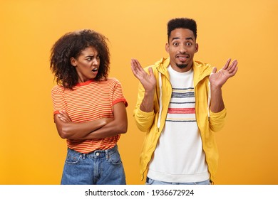 Jeez man what your problem. Offended displeased african american stylish and attractive girlfriend looking at boyfriend acting cool pretending he uninvolved shrugging with sorry look and smiling