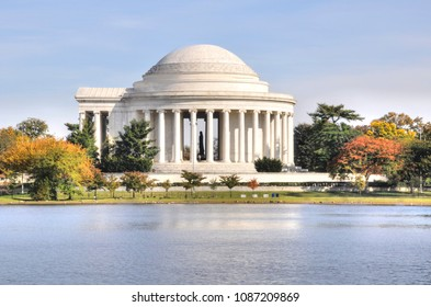 The Jefferson Memorial on the Tidal Basin in Washington DC. The neoclassic  presidential monument is surrounded by colorful trees of an early autumn landscape.