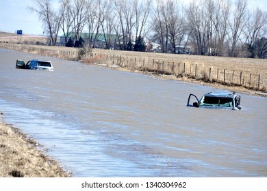 Jefferson, South Dakota / United States - March 16 2019: Two abandoned cars completely submerged in water next to South Dakota I-29 highway after record flooding.