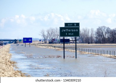 Jefferson, South Dakota / United States - March 15 2019: Flooded highway signs for Jefferson, South Dakota, with two flooded and submerged vehicles visible in the background.