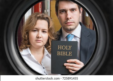 Jehovah witnesses are showing bible behind door. View from peephole.