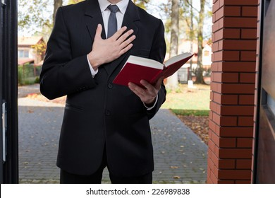 Jehovah's witness standing at the door and holding Bible