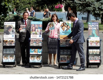 Jehovah's witnesses stand next to a stand with religious magazines and literature on a street in Kiev, Ukraine, 4 August 2019