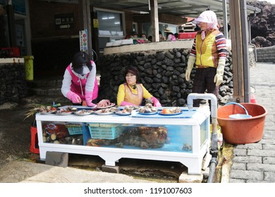 Jeju Island - April 2018 : Group of Haenyeo selling fresh seafood at Jeju woman diver (Haenyeo) performance location in Jeju Island, South Korea. Haenyeo are traditional breath-hold women divers.