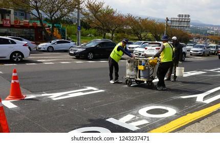 Jeju island, South Korea - April 2018: Workers put markings on the road in Jeju.