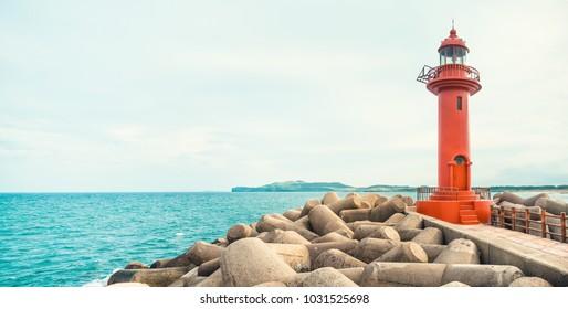 JEJU ISLAND, SOUTH KOREA - AUGUST 18, 2015: Panoramic shot of seascape with red color lighthouse at Jeju Island - South Korea