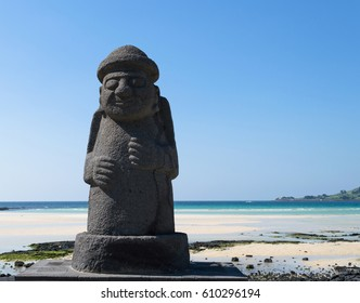 JEJU ISLAND, SOUTH KOREA, SEPTEMBER 10, 2015: statue of Dol hareubang - symbol of Jeju island on sunny day with sea and beach on background