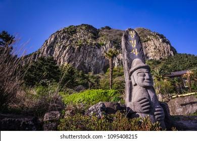 Jeju, South Korea - April 9, 2018: Sanbangsan Mountain with dol hareubang  at Jeju Island, South Korea.