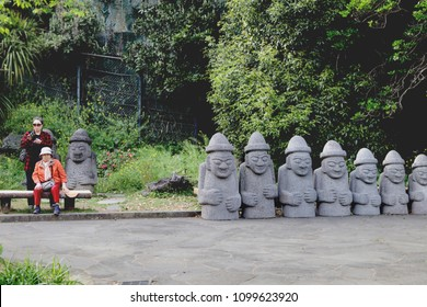 Jeju-do - April 2018 : Old tourist lady sitting on a bench near row of stone-dolls named Dol Hareubang in garden park at Cheonjiyeon waterfall, Jeju Island,South Korea.