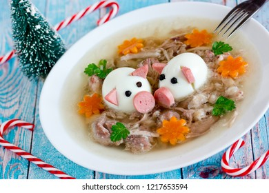 Jellied meat kholodets, meat aspic decorated with boiled eggs shaped funny pigs, carrot flowers and green parsley